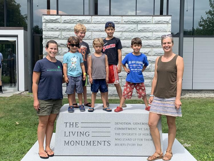Families and school children pose with Rock of Ages The Living Monuments podium