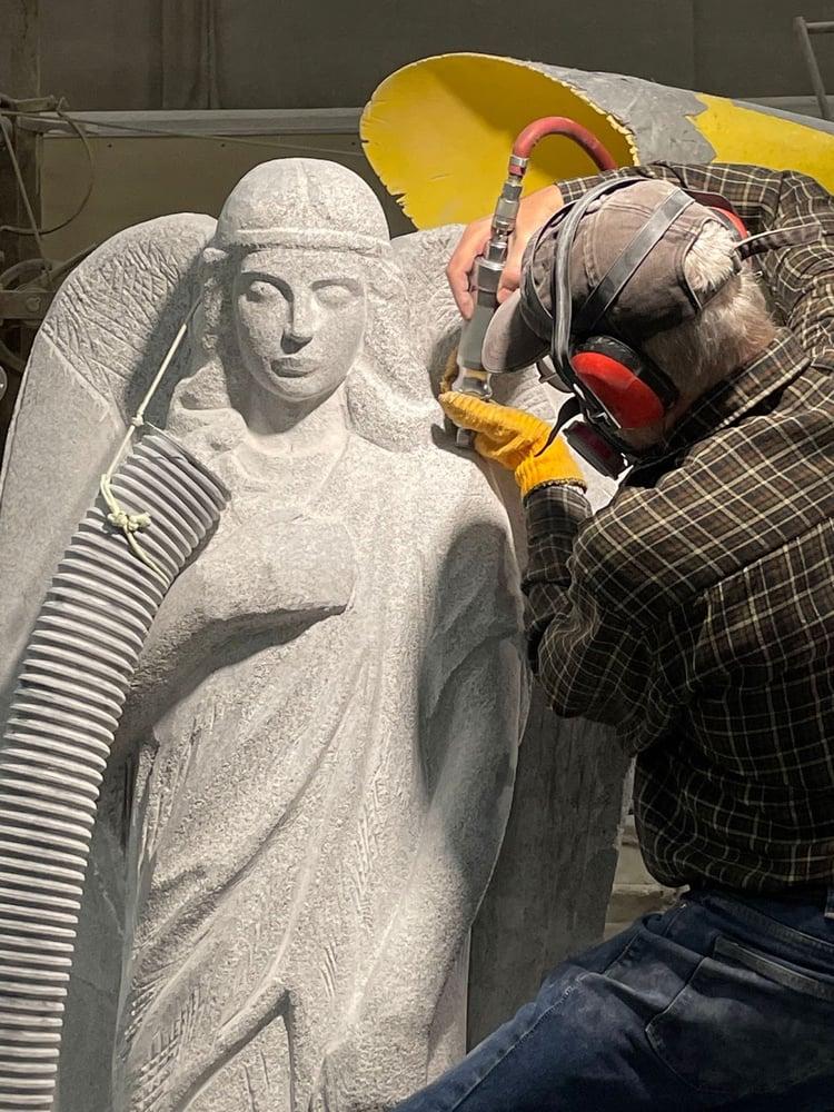 Stanley Lutostanski master stone carver carves angel from Blue Gray granite