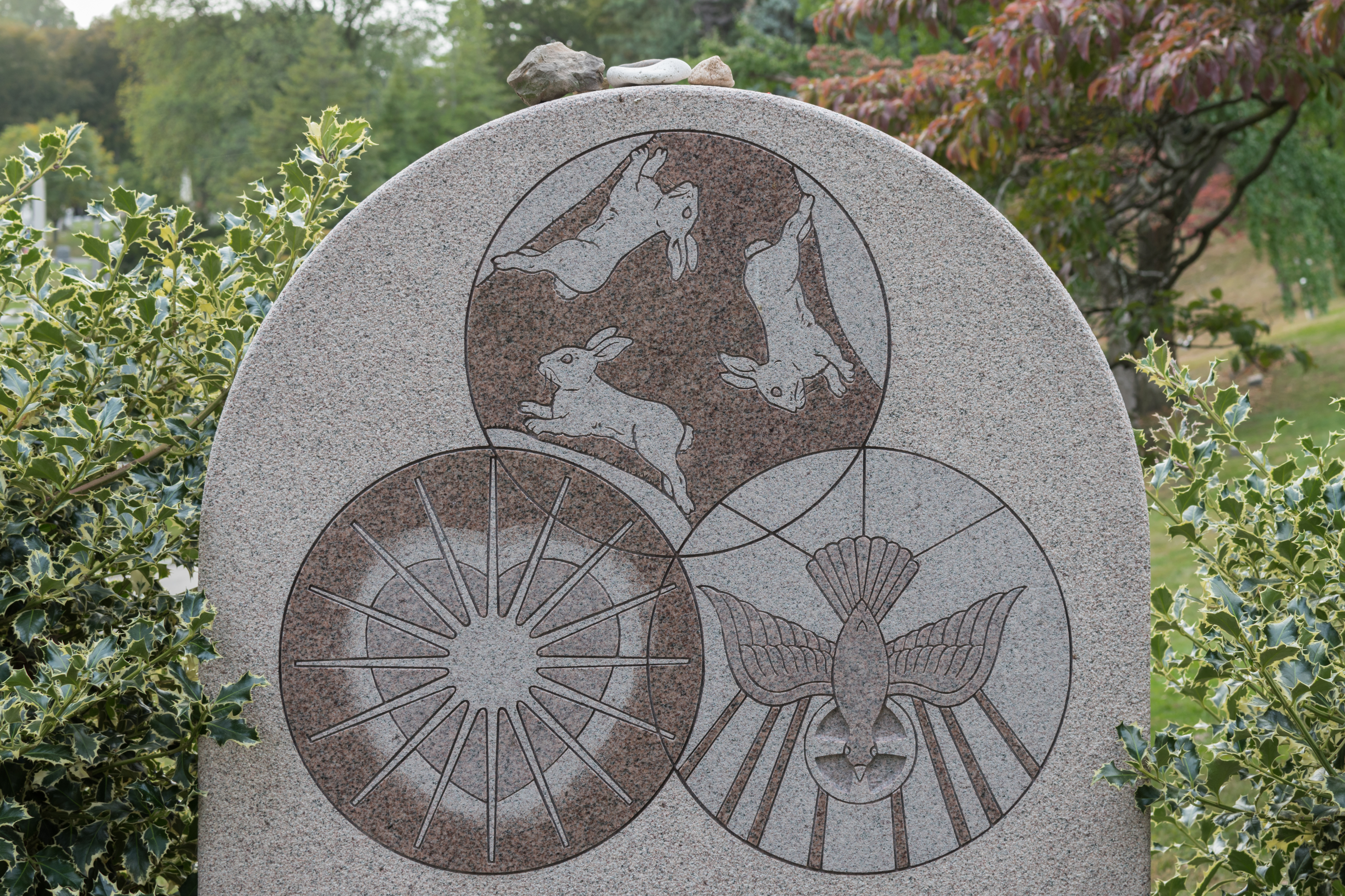 Rabbits, a descending dove, and an intricate heart sit carved into this unique and incredibly detailed custom LAURENTIAN ROSE® granite memorial.