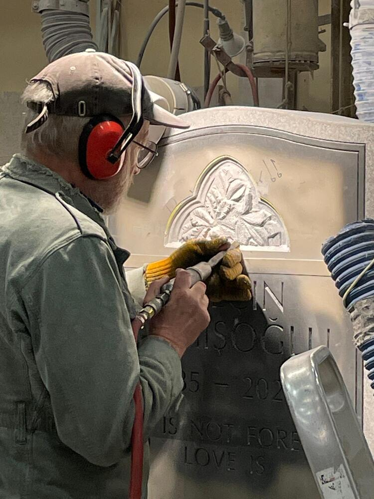 Rock of Ages Master Sculptor Stanley Lutostanski uses pneumatic tools to hand carve a family memorial